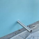 Metallstange, die aus einer blauen Wand heraussteht